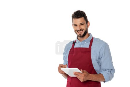 Photo for Smiling waiter looking at camera while using digital tablet isolated on white - Royalty Free Image