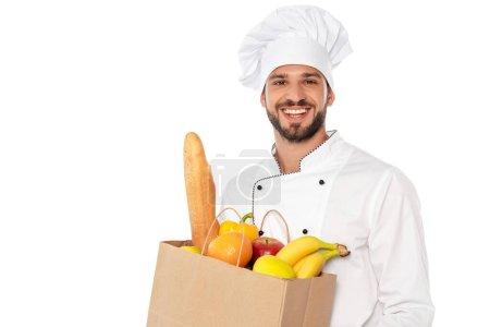 Photo pour Beau chef souriant à la caméra et tenant sac à provisions avec baguette et fruits frais isolés sur blanc - image libre de droit