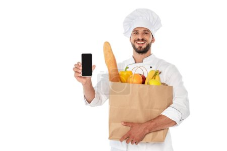 Photo pour Cuisinier souriant tenant un sac à provisions avec de la nourriture et un smartphone isolé sur blanc - image libre de droit