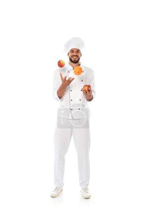 Photo pour Chef souriant jonglant avec des fruits frais sur fond blanc - image libre de droit
