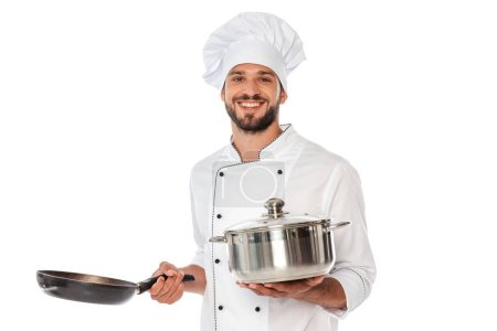 Photo for Smiling chef in uniform holding pan and frying pan isolated on white - Royalty Free Image