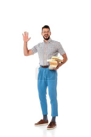 Photo pour Sourire nerd tenant des livres et agitant la main à la caméra sur fond blanc - image libre de droit