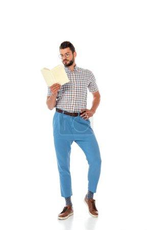 Photo pour Nerd dans les lunettes avec la main sur la hanche livre de lecture sur fond blanc - image libre de droit