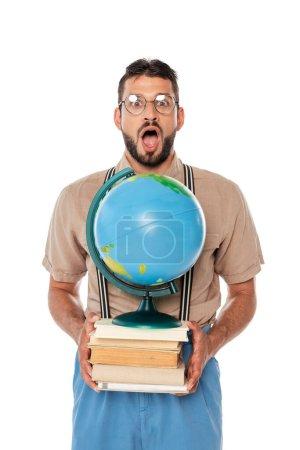 Choqué nerd regarder la caméra tout en tenant globe et des livres isolés sur blanc