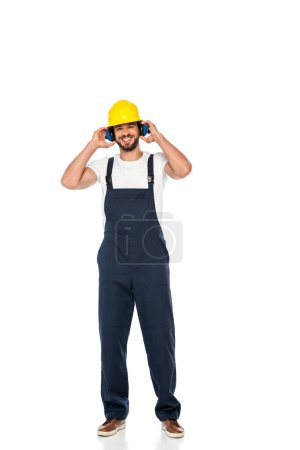 Smiling workman in hardhat and ear defenders looking at camera on white background
