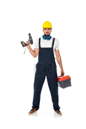 Handsome workman in uniform and hardhat holding electric screwdriver and toolbox on white background