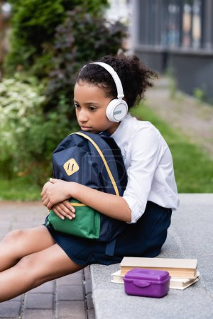 triste africano americano colegiala con mochila y auriculares sentado fuera
