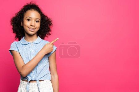 Photo pour Sourire mignon frisé afro-américain enfant pointant avec le doigt de côté isolé sur rose - image libre de droit