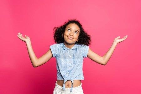 Photo pour Sourire mignon frisé afro-américain enfant montrant geste haussant les épaules isolé sur rose - image libre de droit