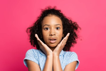 shocked cute curly african american kid with hands near face isolated on pink