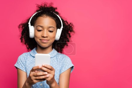 Photo for Smiling curly african american kid in headphones using smartphone isolated on pink - Royalty Free Image