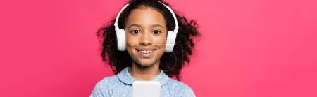 Photo for Smiling curly african american kid in headphones using smartphone isolated on pink, panoramic shot - Royalty Free Image