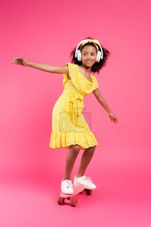 full length view of smiling curly african american child in yellow outfit and headphones riding penny board on pink background