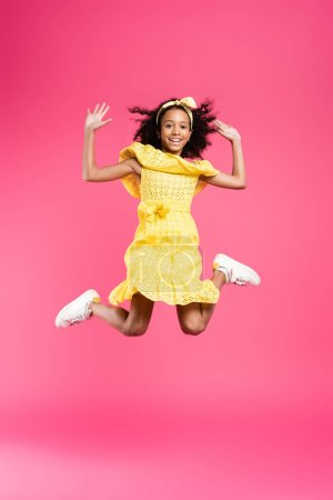 Photo for Full length view of happy curly african american child in yellow outfit jumping on pink background - Royalty Free Image