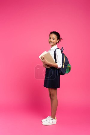 Photo pour Vue latérale de l'écolière afro-américaine souriante avec sac à dos et livres sur fond rose - image libre de droit