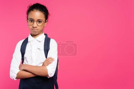 Photo pour Offensé afro-américaine écolière dans des lunettes avec sac à dos et les bras croisés isolés sur rose - image libre de droit