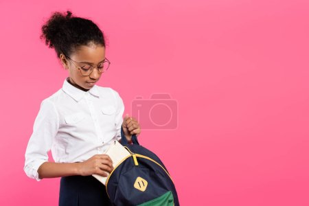 african american schoolgirl in glasses putting book in backpack isolated on pink