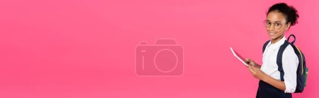 Photo for Smiling african american schoolgirl in glasses with backpack using digital tablet isolated on pink, panoramic shot - Royalty Free Image