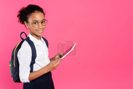 Photo for Smiling african american schoolgirl in glasses with backpack using digital tablet isolated on pink - Royalty Free Image