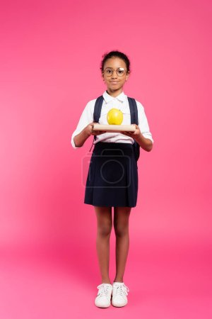 smiling african american schoolgirl in glasses with book and apple on pink