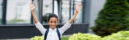 Photo pour Souriant afro-américaine écolière avec sac à dos et les mains en l'air à l'extérieur, vue panoramique - image libre de droit