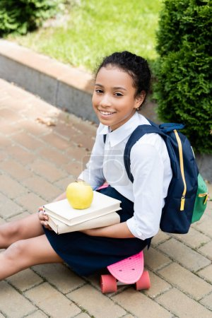Photo for Smiling african american schoolgirl with books and apple sitting on penny board - Royalty Free Image