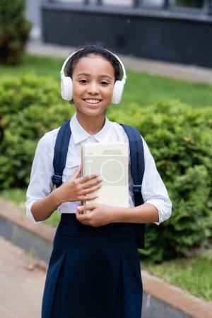 Photo pour Souriant afro-américaine écolière dans des écouteurs avec sac à dos et livres à l'extérieur - image libre de droit