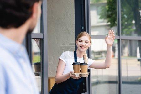 Photo pour Concentration sélective de serveuse souriante tenant des tasses en papier et agitant la main à l'homme près du café - image libre de droit