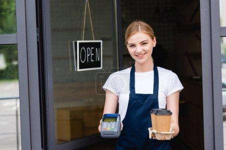 Photo pour Serveuse souriante tenant terminal de paiement et café pour aller près de l'enseigne avec lettrage ouvert sur la porte du café - image libre de droit