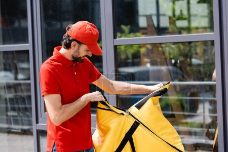 Smiling courier opening thermo bag on urban street
