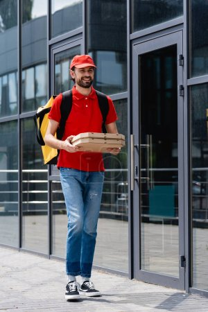 Smiling courier with thermo backpack holding pizza boxes while walking near building on urban street