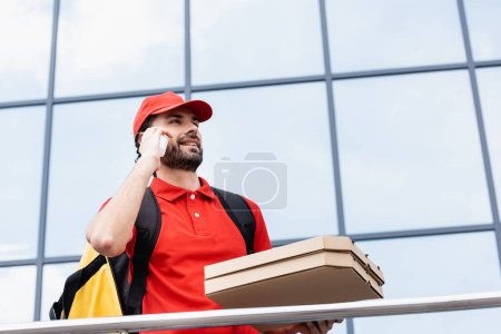Low angle view of smiling courier talking on smartphone while holding pizza boxes on urban street