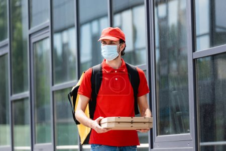 Delivery man in medical mask holding pizza boxes on urban street