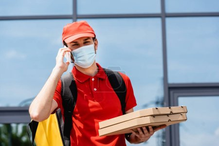 Courier in medical mask talking on smartphone and holding pizza boxes on urban street