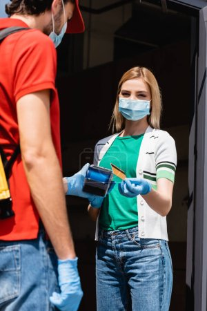 Selective focus of woman in medical mask holding credit card near courier with payment terminal on urban street