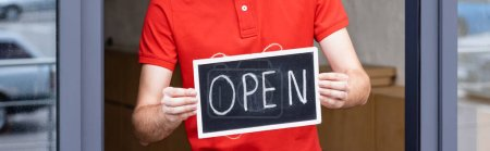 Photo for Panoramic shot of waiter holding signboard with open lettering near cafe on urban street - Royalty Free Image