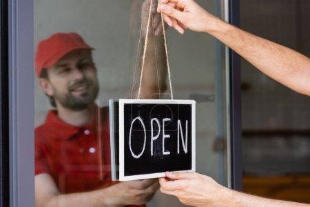 Photo pour Foyer sélectif du serveur souriant pendaison enseigne avec lettrage ouvert sur la porte du café - image libre de droit