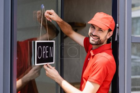 Photo pour Vue latérale du serveur positif en uniforme enseigne suspendue avec lettrage ouvert sur la porte du café - image libre de droit