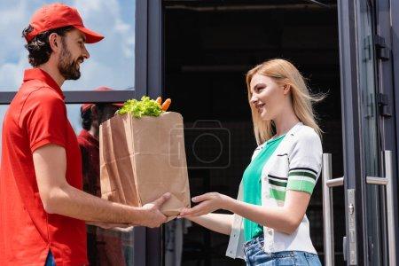 Photo pour Courrier souriant donnant un sac à provisions avec des légumes à une jeune femme près d'un immeuble dans une rue urbaine - image libre de droit