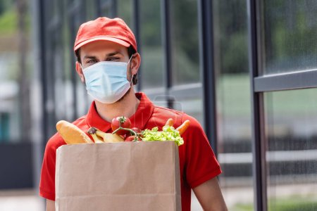 Photo for Courier in medical mask holding shopping bag with fresh vegetables on urban street - Royalty Free Image