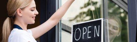 Photo pour Vue panoramique de serveuse souriante suspendue enseigne avec lettrage ouvert sur la porte du café - image libre de droit