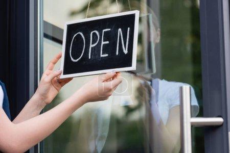 Photo pour Vue recadrée de serveuse suspendue enseigne avec lettrage ouvert sur la porte du café - image libre de droit