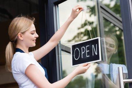Photo pour Vue latérale de la serveuse souriante dans un tablier suspendu enseigne avec lettrage ouvert sur la porte du café - image libre de droit