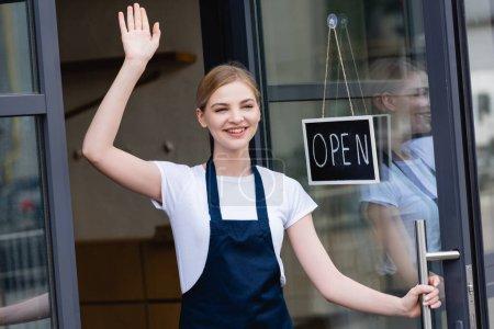 Photo pour Serveuse positive agitant la main près de l'enseigne avec lettrage ouvert sur la porte du café - image libre de droit