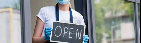 Panoramic shot of waitress in latex gloves and medical mask holding signboard with open word near window of cafe