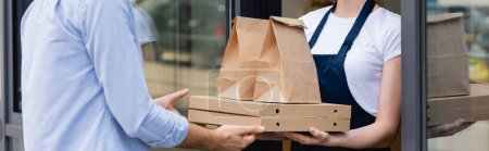 Photo for Panoramic shot of man receiving pizza boxes and paper bags for takeaway from waitress near window of cafe - Royalty Free Image