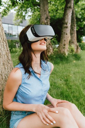 Photo for Happy young woman in virtual reality headset sitting near green trees - Royalty Free Image