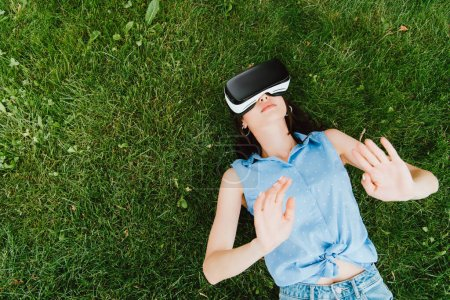 Photo pour Vue de dessus de la jeune femme en réalité virtuelle casque geste et couché sur l'herbe verte - image libre de droit