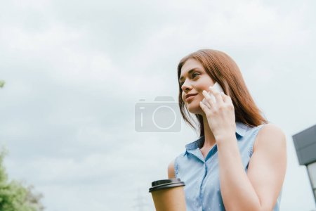 Photo for Low angle view of businesswoman holding paper cup and talking on smartphone against cloudy sky - Royalty Free Image