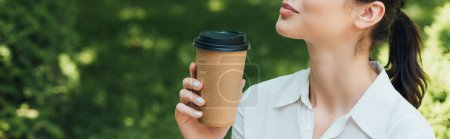 panoramic crop of businesswoman holding paper cup with coffee to go